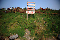 Signboards put up by locals by the side of the dam, complaining about the drilling company that accidentally started the mud flow that destroyed their homes, and the fact that they are still owed 80 percent of the compensation money promised to them. Since May 2006, more than 10,000 people in the Porong subdistrict of Sidoarjo have been displaced by hot mud flowing from a natural gas well that was being drilled by the oil company Lapindo Brantas. The torrent of mud - up to 125,000 cubic metres per day - continued to flow three years later.
