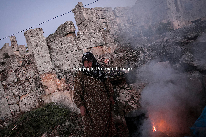 "In this Thursday, Sep. 26, 2013 photo, a Syrian displaced woman cooks a meal for dinner in the sunset at the Kafr Ruma, an ancient roman ruins used as temporary shelter by those families who have fled from the heavy fighting and shelling in the Idlib province countryside of Syria. Dozens of families settled in the ancient ruins known as ""The Forgotten City"" and declared human heritage by UNESCO, when the clashes between opposition fighters and government forces broke out in the region since more than two years ago. (AP Photo)"