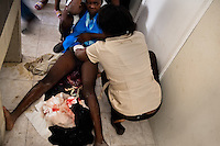 An 18-years old Haitian girl lies on the floor exhausted after giving birth to her first baby while waiting for free food in a feeding center in Port-au-Prince, Haiti, 17 July 2008.