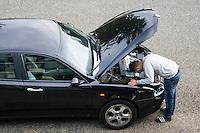 Nederland, Zeist, 10 okt  2014<br /> Man met autopech precies voor m'n deur. Hij belt om hulp bij openstaande motorklep en probeert zelf iets te verhelpen.<br /> <br /> Foto: (c) Michiel Wijnbergh