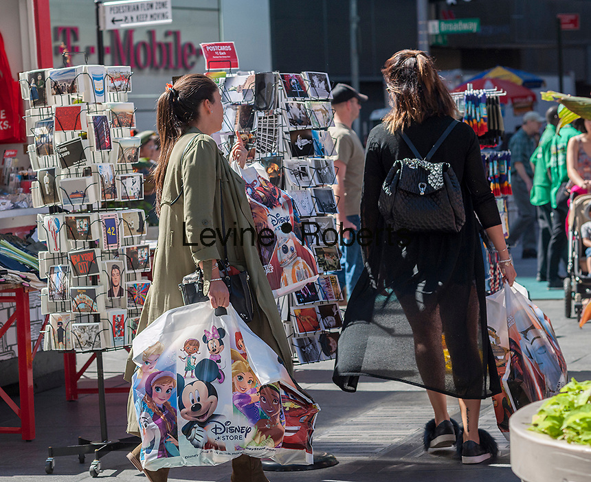 Visitors to Times Square in New York with their Disney Store purchases on Thursday, September 15, 2016.  U.S. retail sales for August were below analysts' expectations as automobile and gasoline sales were weak and shoppers abandoned their spending spree from the spring.  (© Richard B. Levine)
