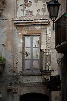 Detail of a ruined facade and window in a narrow street in Ortigia, Syracuse, Sicily, pictured on September 13, 2009, in the afternoon. The 2,700 year old Syracuse is a province and a city in southern Italy on the Island of Sicily. The island Ortigia is the historic centre of Syracuse. Today the city is a UNESCO World Heritage Site. Founded by Ancient Greek Corinthians and allied with Sparta and Corinth, it was a very powerful city-state and one of the major powers of the Mediterranean.  In the 17th century it was heavily destroyed by an earthquake. Many buildings date back to the  19th century when it regained importance. Picture by Manuel Cohen.