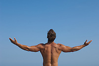 Shirtless back of young man standing with his arms outstrethed against a clear blue sky