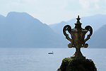 A view of Lake Como, Italy with a person standing on a small boat. This view is taken from the gardens of Villa del Balbianello on Lake Como, Italy.