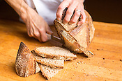 Hillsborough, North Carolina - Friday September 4, 2015 - Rob Nichols, Weaver Street's bread production manager, demonstrates the proper way to cut a loaf of miche.