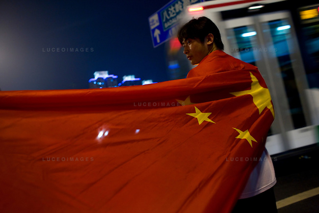 A Chinese Olympic fan wait to catch a glimpse of the opening ceremony fireworks in Beijing, China on Friday, August 8, 2008.  Kevin German