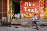 The young boy in India sits in front of the shutter of a storefront that is painted with the words &quot;nice touch&quot;.