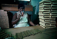 December 1981, Havana, Cuba --- A cigar maker at the Montecristo factory lights up a cigar to smoke as she works. --- Image by &copy; Owen Franken/CORBIS