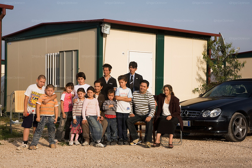 Carlo and Balo Cizmic, Roma ambassadors representing Italian Roma at European diplomatic level, pictured with their extended family. Roma Gypsies victims of racism and discrimination, often forcibly evicted or moved from one camp to another, marginalized, living on the periphery of urban centres. The Roma Gypsies originated from India where they left over a thousand years before. Tribes moved across Euroasia eventually arriving in Europe in the 14th century. They have survived 500 years of slavery and persecution. They moved from place to place, often nomadic in search of work. Now many live in container camps, some are unemployed, others work the markets, or import export. Rome, Italy.