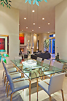 Vertical image of dining room that leads into living room in modern residence.
