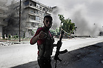 SYRIA, ALEPPO : A rebel from the Free Syrian Army prevents people  from approaching the area being hit by mortar shelling, on September 26, 2012. ALESSIO ROMENZI