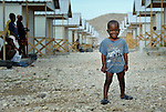 Robert Colin, 3, stands in the street of the Corail resettlement camp north of Port-au-Prince, Haiti. Residents of the camp, survivors of the devastating January 2010 earthquake, were relocated to the remote location from overcrowded tent cities for the homeless in the nation's capital. Yet shortly after its establishment, thousands of homeless families from around the capital region moved to the area and began constructing their simple homes around the edges of the official camp, creating a complex set of questions for camp managers. The United Methodist Committee on Relief, a member of the ACT Alliance, has built schools in the camp and is providing school furniture, teacher training, and educational materials for students. Colin stands between rows of transitional homes--houses designed to get quake survivors into homes quickly, yet which residents will be expected to modify and improve in coming years.