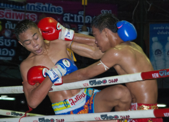 Bangkok, August 30, 2011, Lumpini Muay Thai kick boxing stadium, Akemongkol (in the red gloves) lands a blow on his opponent Yodvicha