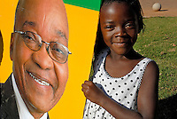 A young girl stands beside a picture of Jacob Zuma at an African National Congress (ANC) election rally held at the Ellis Park Stadium in Johannesburg..