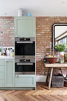 Pale green bespoke units compliment the rustic collection of objects, flower arrangements and bare brick walls in Kally Ellis's kitchen