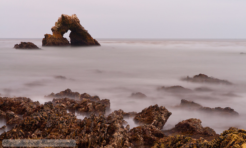 This long exposure image captures a differnet view of rocks in the intertidal: instead of being hit by waves, the rocks look like they're shrouded in a low mist or fog.  I love how it links the foreground intertidal rocks to the background arhced rock that's offshore.