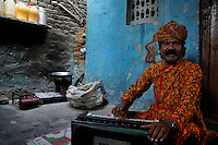 Babulal Bhaat is a Mand singer (Classical welcome song from Rajasthan) from Katputly colony in New Delhi, India. 14.11.2009. Kathputly colony is a slum area in West Delhi. This slum seems like any other slum areas of modern India with dysfunctional electricity, non existing sanitation and poverty. As a part of Delhi, this is also ailed with water crisis. Large families live their lives crammed together in a single room with all the odds which complement poverty. One thing which differentiates this slum with any other is the people living in the colony. Nearly everybody in this slum is a traditional performing artist; and they have been migrating to this area for last 50 years from different parts of the country for a better livelihood. They are magicians, acrobats, jugglers, puppeteers, dancers and musicians. These artistes perform in star rated hotels, marriage ceremonies of the richer section, functions, and festivities all around the country and the world. Most of the artisans I met here, have performed in Europe and America but such opportunities are rare to come by. They struggle to keep their art form alive. They say that they don't get any help or support from the government for their basic needs and for the well being of the Kathputly colony -  though they have uphold the prestige of the country internationally. Polluted air, dirty alleys smelling of urine, colourful dress and sound of music characterise Kathputly colony, which is the one of its kind in India. Arindam Mukherjee