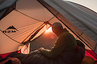 Hiker awakes at sunrise in tent on summit of Skierfe, Sarek National Park, Lapland, Sweden