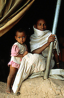 Eritrea. Southern Debud Zone. Maiwuray. People and families live in tents, because they are IDP (Internaly Displaced People) from the war on a border dispute(1999 to 2001) between Eritrea and Ethiopia. Mother wears a white loincloth around her neck while her daughter has a pink dress. © 2002 Didier Ruef