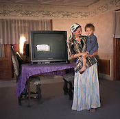 A Roma woman, holding her son, stands in a room of her new home, beside a large television, in the Roma camp of Sintesti. Over 100 new houses have been built within the last 7 years in the camp, financed by the profits of scrap metal dealing..