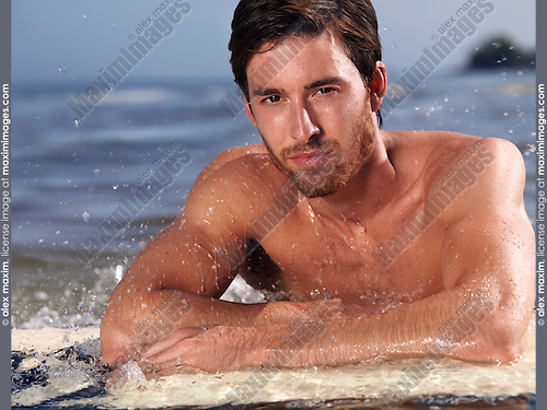 Portrait of a young man with a surfboard in water. Summer lifestyle