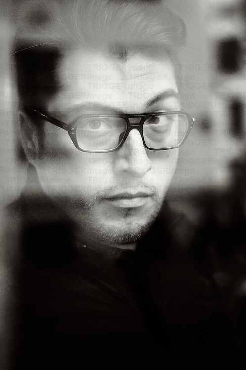 portrait of a man with glasses sitting behind a window pane looking into the cam.