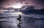 Man with metal detector cycling along beach Photographs of the Isle of Wight by photographer Patrick Eden