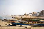 Colorfully-painted boats line the beach of Yoff, a fishing village 30 minutes outside of Senegal's capital city of Dakar.  The green topped  Seydina Limamou Laye Mausoleum is seen in the distance.