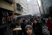 Uighurs walk through a small outdoor food and goods market in the Uighur section of Urumqi, Xinjiang, China.  The city is divided between Han and Uighur ethnic groups and in 2009 saw violent clashes between the groups.