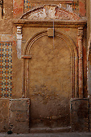 """Detail of a bricked up doorway with pediment decorated with carved foliage and old ceramics, old city, Portuguese Fortified city of Mazagan, El Jadida, Morocco. El Jadida, previously known as Mazagan (Portuguese: Mazag""""o), was seized in 1502 by the Portuguese, and they controlled this city until 1769. Picture by Manuel Cohen"""
