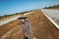 A girl walks between lanes of an empty highway connecting the old Myanmar's capital Yangon and new capital Naypyitaw November 30, 2011. Hillary Clinton became the first U.S. secretary of state to visit Myanmar in more than 50 years on Wednesday, launching an historic mission to press the reclusive country's new leaders to sever illicit contacts with North Korea and deliver on reforms.   REUTERS/Damir Sagolj (MYANMAR)