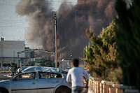 Syrian civilians watch the shelling by Syrian army aircraft over a swiming pool compund outskirst of the Maali village at north of Aleppo province.
