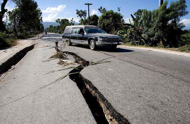 Cars passing a road damaged by the Jan. 12 earthquake in the coastal town of Leogane, south of Haiti's capital Port-au-Prince on January 29, 2010.