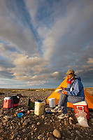 Alaskan author Debbie Miller at camp along the Etivluk river in Alaska's midnight sun, National Petroleum Reserve, Alaska.
