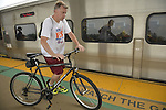 During evening rush hour, a man walks with his bicycle on elevated platform to board train at Merrick train station of Babylon branch, after MTA Metropolitan Transit Authority and Long Island Rail Road union talks deadlock, with potential LIRR strike looming just days ahead.