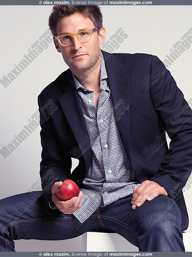 Fashionably dressed man in his thirties wearing jeans and a stylish jacket holding an apple in his hand