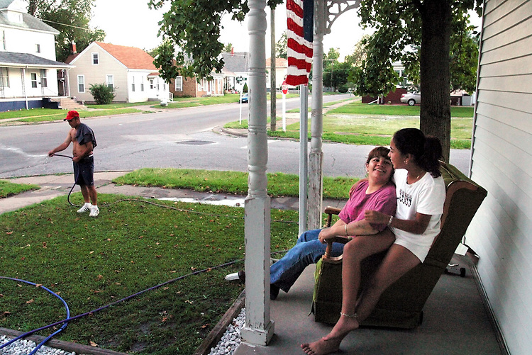"""This is the American dream and we are living it,"" said Marisela Chavez, enjoying a quiet summer evening with Stephanie, 11, one of her three daughters. Chavez came to Beardstown in 1995; she works for the school system's bilingual program and her husband Valentine, left, works at Excel. Like many Mexican families in Beardstown, they purchased a home next to Caucasian neighbors and adopted local customs, such as flying the flag and maintaining their lawn."