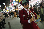 'Chindonya' musician plays a clarinet to advertise a new Pachinko gaming parlor, in Shibuya district of Tokyo, Japan, on Saturday, Nov. 18, 2006.