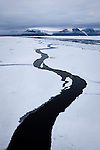 A pathway opens in the landfast sea ice, forming question mark in Dijmhna Sund, Nioghalvfjerdsfjorden, in Greenland&rsquo;s remote northeast corner.  The Arctic Ocean sea ice continues to decline. As more white ice, which reflects sunlight back into space is lost, the remaining dark water absorbs heat, creating a feedback effect spells bad news for the Arctic, and the global climate. Greenland, 2009<br />