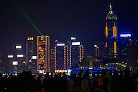 The skyscrapers along Hong Kong island's harbour waterfront at night, with fa&ccedil;ades covered with decorative lighting designs for Christmas and laser searchlights for the nightly Symphony of Lights show, viewed by crowds of people across the harbour in Tsim Sha Tsui