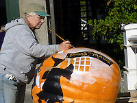 Artist paints very large pumpkin as part of the pumpkin festival, Damariscotta Maine