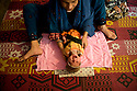 Ghair Bibi's daughter wraps her two-month-old baby in a towel. <br />