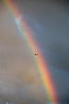 Airplane flying through rainbow