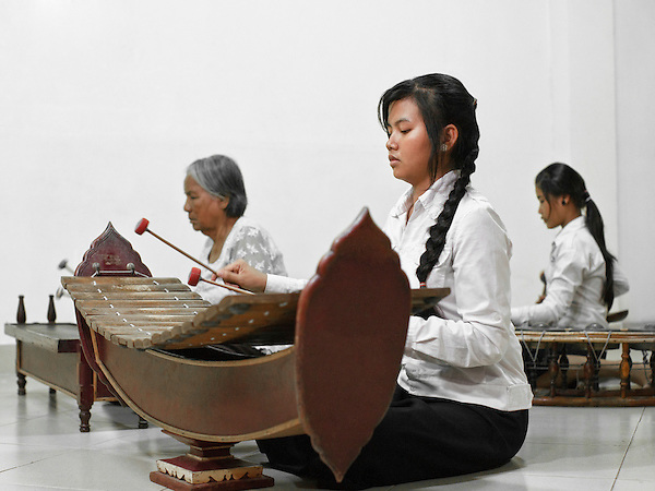 "Pinpeat Music Class at Cambodia Living Arts House. Phnom Penh, Cambodia. Left: The Roneat Thoung is a tuned percussion instrument made of wood. This instrument plays an important part in the ""Pin Peat"" and ""Mohowrri"" orchestras. Far Right: Korng Thomm  ( aka Kong vong toch )A small gong circle from Cambodia. Cambodian Living Arts works to support the revival of traditional Khmer performing arts and to inspire contemporary artistic expression. CLA supports arts education, mentorship, networking opportunities, education, career development, and income generating projects for master performing artists who survived the Khmer Rouge as well as the next generation of student artists."