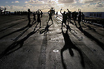 """Marines take part in early morning excercise referred to as """"PT"""" for physical training - one of a dizzying array of acronyms used by the Corps. Aboard ship, Marines are required to take part in PT six days a week, often while carrying their weapons and fully dressed in boots and body armor, to prepare themselves for the rigors of the upcoming deployment in the heat and dust of Iraq."""