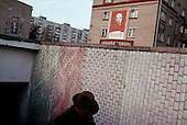 Moscow, Russia<br /> October 21, 1992<br /> <br /> A Lenin poster hangs over a small market in the Moscow suburbs.<br /> <br /> In December 1991, food shortages in central Russia had prompted food rationing in the Moscow area for the first time since World War II. Amid steady collapse, Soviet President Gorbachev and his government continued to oppose rapid market reforms like Yavlinsky's &quot;500 Days&quot; program. To break Gorbachev's opposition, Yeltsin decided to disband the USSR in accordance with the Treaty of the Union of 1922 and thereby remove Gorbachev and the Soviet government from power. The step was also enthusiastically supported by the governments of Ukraine and Belarus, which were parties of the Treaty of 1922 along with Russia.<br /> <br /> On December 21, 1991, representatives of all member republics except Georgia signed the Alma-Ata Protocol, in which they confirmed the dissolution of the Union. That same day, all former-Soviet republics agreed to join the CIS, with the exception of the three Baltic States.