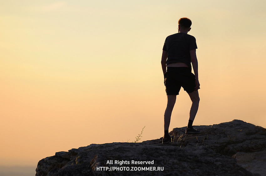 "Male silhouette on hiest hill of the Zhiguli mountains on sunset. Russian National Park ""Samarskaya Luka"""
