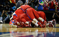 The Dayton Flyers celebrate after winning the second-round NCAA Tournament game between the Ohio State Buckeyes and the Dayton Flyers at the First Niagara Center, Thursday afternoon, March 20, 2014. The Dayton Flyers defeated the Ohio State Buckeyes 60 - 59. (The Columbus Dispatch / Eamon Queeney)