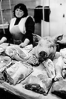 Ukraine. Province of Kiev. Slavutich. Butcher's stall in the food market. Raw meat and a pig head for sale. Saleswoman. The town of Slavutich was created after the catastrophe which took place on april 1986 at 1.23 am with the explosion of reactor No 4 at Chernobyl atomic power station. Slavutich is distant 60 km from the power station and was newly built after the evacuation of the inhabitants from both towns of Pripyat and Chernobyl.  © 2006 Didier Ruef