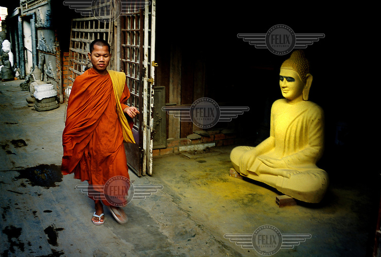 Monk passing a Buddha figure in the final stages of completion, half-painted in the front of a workshop of one of the Prayuvong Buddha factories.